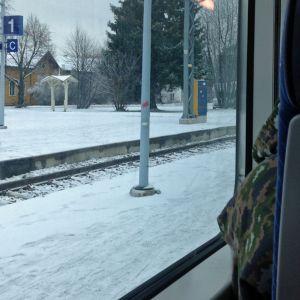 Kajaanin rautatieaseman kyltti junan ikkunasta kuvattuna.