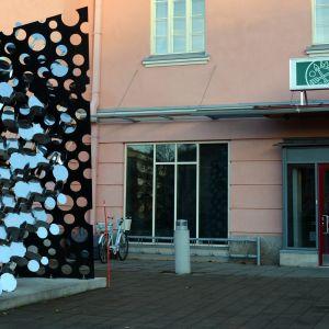Kuopion verotoimiston ulko-ovi ja oven edessä oleva taideteos.
