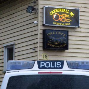 Seinällä kyltit Cannonball MC Hämeenlinna ja Outfit MC Hämeenlinna, etualalla poliisiauto