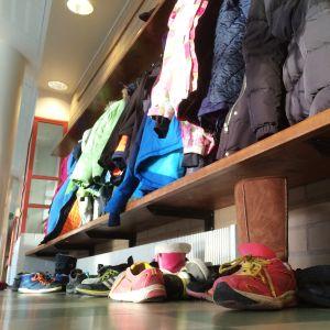Koululaisten takkeja ja kenkiä naulakossa.