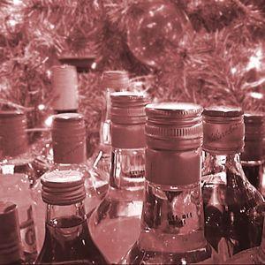 Vaaleanpunaiseksi sävytetty kuva alkoholipulloista kuusenoksien ja jouluvalojen keskellä.
