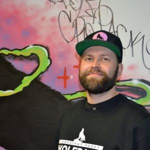 Mies seisoo susigraffitin edessä.