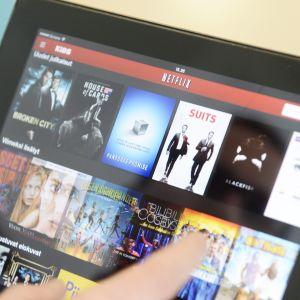 Mies selaa ohjelmia Netflix-palvelusta.