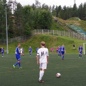 Nuorten jalkapallo-ottelu. Keltapaitainen tuomari vasemmalle. Kentällä sini-ja valkoasuisia pelaajia.