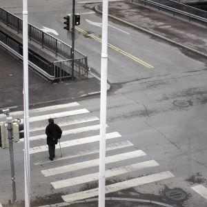 Yksinäinen vanhus kävelee suojatiellä.