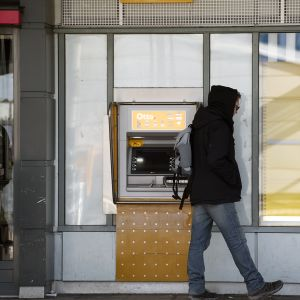Mies seisoo raha-automaatin edustalla.