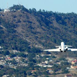 Matkustajakone nousee kohti vuorenrinnettä.