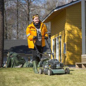 Postin työntekijä leikkaamassa ruohoa.
