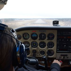 Pienkone laskeutumassa kentälle, lentäjäoppilas Jenny Hirsikangas ohjaamossa.