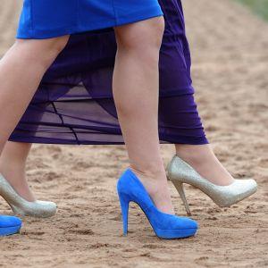 Kuva kahden korkokengissä kävelevän naisen jaloista.