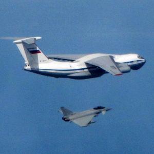 Ison kuljetuskoneen alapuolella lentää hävittäjä. Kuljetuskoneen peräsimessä on Venäjän lippu.