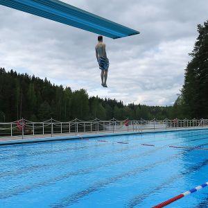 Mies hyppää hyppytornista altaaseen maauimalassa