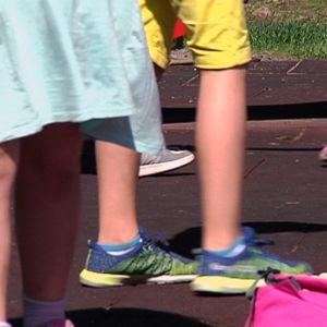 Lasten jalkoja koulun pihalla.