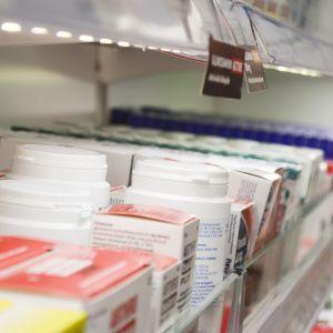 Lääkkepurkkeja ja laatikoita apteekin hyllyllä