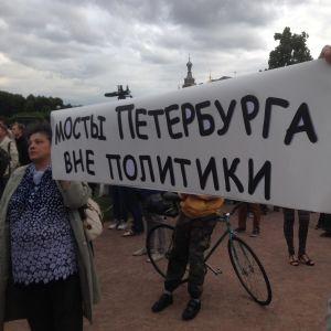 Mielenosoittajat kantavat kylttiä, jossa vaaditaan pitämään Pietarin sillat erossa politiikasta.