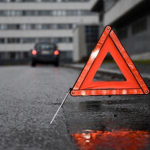 Punaisena hohkuva varoituskolmio kadulla.