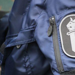 Poliisin logo poliisimiehen hihassa.