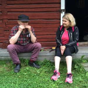 Nainen ja mies istuvat kotiseutumuseon rakennuksen edessä.