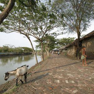 Kivetty joenpiennar ja savitalojen seiniä. Kadulla kävelee lannevaatteeseen pukeutunut poika, joen rannalla vuohi katselee veteen.