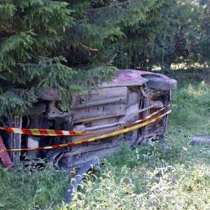 Poliisinauhalla eristetty onnettomuusauto kyljellään metsänreunassa