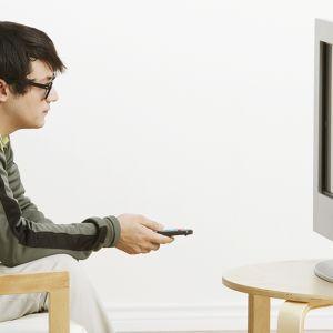 Nuori mies katselee televisiota.