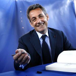 Nicolas Sarkozy katsoo kameraan ja virnistää.