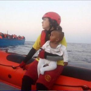 Nainen lapsi sylissään veneessä, taustalla ihmisiä täynnä oleva vene.