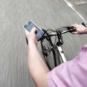 Pyöräilijä selaa Facebookia ajaessaan.