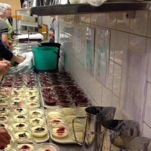 Oppilaita annostelemassa jälkiruokaa astioihin.