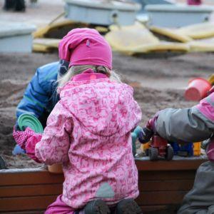 Lapsia tarhassa hiekkalaatikolla.