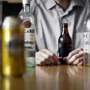 Mies istuu olutpullo edessään pöydän äärellä.