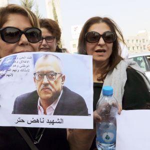 Naiset pitelivät ammutun kirjailijan Nahed Hattarin kuvaa Fuhaisissa, Jordaniassa sunnuntaina.