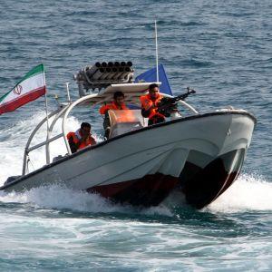 Kolme miestä oransseissa pelastusliiveissä on kovaa vauhtia etenevässä moottoriveneessä. Yksi miehistä on ruorissa, yksi pitelee konekivääriä ja yksi istuu takana. Veneessä on Iranin lippu.