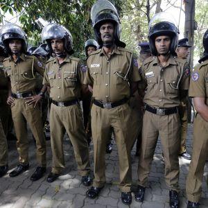 Rivi poliiseja khakiunivormuissa ja mellakkypärissä.