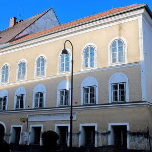 Kellertävä kivirakennus, jossa on kaari-ikkunat ja punainen katto.