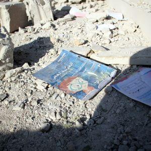 Kivimurskaa maassa, keskellä kivipölyn harmaannuttama koulukirja.