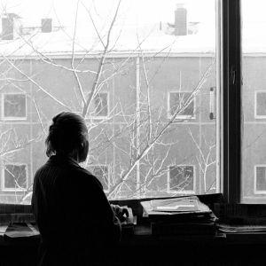 Nainen katsoo ikkunasta ulos.