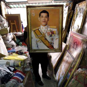 Myyjä esittelee kehystettäy valokuvaa kruununprinssi Maha Vajiralongkornista bangkokilaisessa kaupassa.