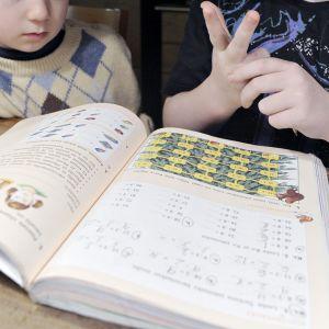 Lapset tekevät matemiikan läksyjä.