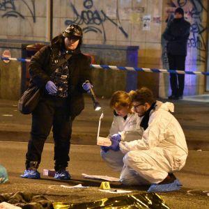Rikostutkijat keräävät todisteita ampumispaikalla.