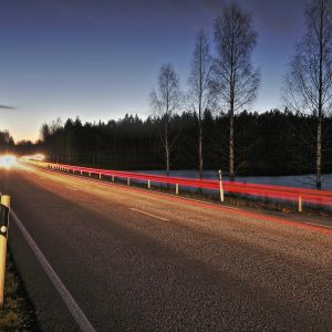 Pimenevässä illassa ajavia autoja.