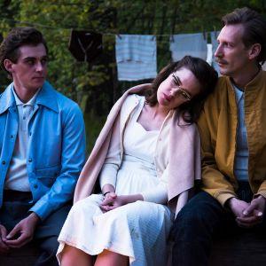 Kahden miehen välissä istuu nainen ja hän nojaa toisen miehen olkapäätä vasten.