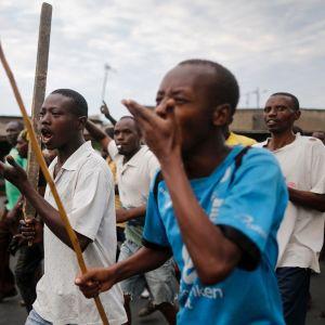 Miehet osoittavat mieltä kadulla pitkät kepit käsissään.