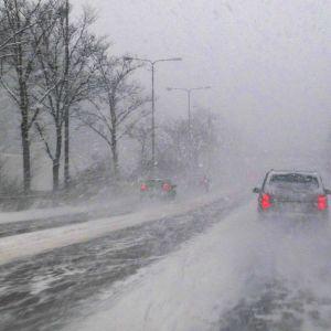 Autoja lumisateessa kehä 1 tiellä.