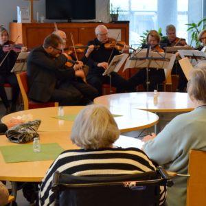 Vanhukset kuuntelevat kaupunginorkesterin konserttia.