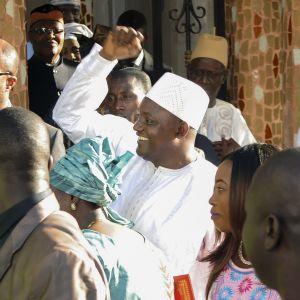 Valkoisiin pukeutunut hymyilevä Adama Barrow heiluttaa kättään. Ympärillä on useita ihmisiä.