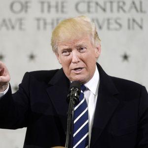 Trump puhuu osoittaen kuulijoita oikean kätensä etusormella. Taustalla näkyy CIA:n päämajan seinää, jossa muistetaan tähdillä palveluksessa kuolleita CIA:n työntekijöitä.