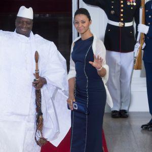 Jammeh ja hänen puolisonsa seisovat punaisella matolla ja tervehtivät ihmisiä hymyillen.