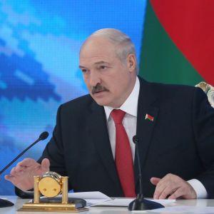 Lukašenka puhuu toimittajille. Taustalla näkyy Valko-Venäjn lippu.