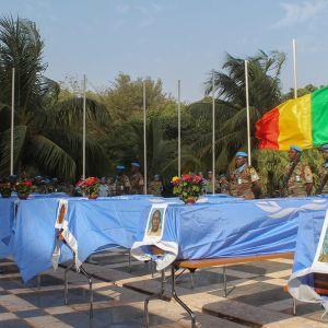 YK:n sinisillä lipuilla peitettyjä ruumisarkkuja, Malin lippu puolitangossa
